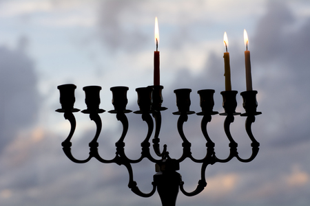 chanukkah: Hanukkah menorah with three burning candles on the second day of Hanukkah.
