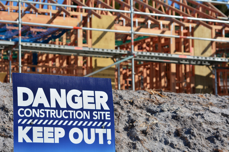 construction work: Danger building site sign in a new home construction site. Concept photo of Building a new home,mortgage, finance, economy, market, construction work, health and safety.