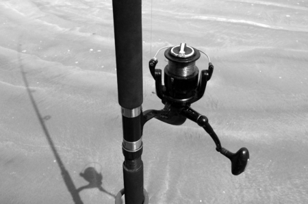 fishing pole: Surfcasting, cast fishing pole rod line and its shadow on sandy beach.Concept photo of angling fishing fish.