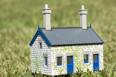subprime mortgage crisis: House on green grass. Concept photo of Real estate market bubble , booming, rent, money,price, grid, home, house, housing, industry and subprime mortgage crisis. (Copy Space)