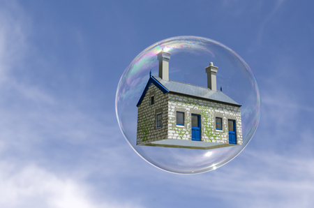 subprime mortgage crisis: House in a bubble fly in the air. Concept photo of Real estate market bubble , booming, money,price, rent, grid, home, house, housing, industry and subprime mortgage crisis. (Copy Space).