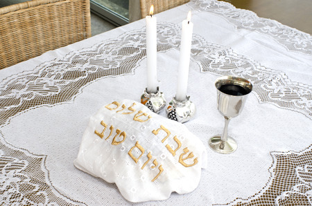 challah: Shabbat eve table with covered challah bread, candles and cup of wine.