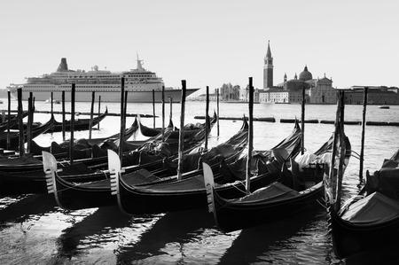 city park boat house: Cruise ship sail near the Island of San Giorgio Maggiore with Venetian Gondolas in the foreground in Venice, Italy. (BW