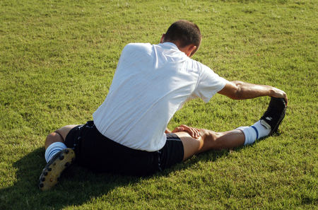 outdoor training: Soccer player is starching and worming up before a football game. .