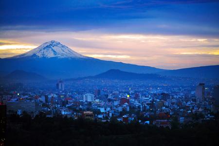 夜景のポポカテペトル火山山の背後にあるメキシコシティ。