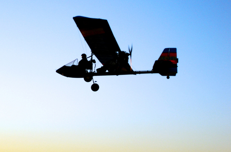 airplane ultralight: A silhouette of microlight glider aircraft fly in the sky during sunset. Stock Photo
