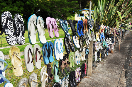 swimming shoes: The iconic jandal fence in Kaeo, New Zealand. A tribute to the New Zealand Jandal that is worn by a large percent of the kiwi or New Zealand population.