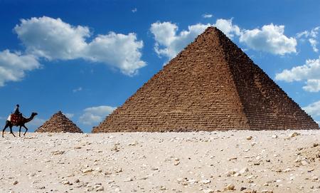 Un homme qui traverse un chameau se promène devant les pyramides emblématiques de Gizeh en Égypte