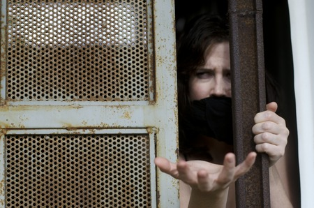 are trapped: A woman trapped in a prison jail cell with a mouth cover Stock Photo