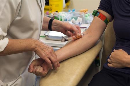 prueba de embarazo: Mujer joven que tiene prueba de sangre en una clínica.