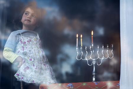 hanoukia: Hanukkah menorah with three burning candles on the second day of Hanukkah.