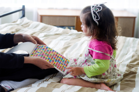 rewarded: Little girl been rewarded for good behavior by her mother with colorful stickers.