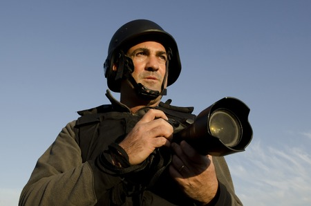 bullet camera: A male press photographer wears a protective helmet and vest and takes photos with a professional camera Stock Photo