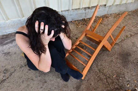 domestic violence: A sad woman is sitting alone on the cold concrete behind a shed Stock Photo