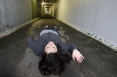 corpse: Crime scene concept photo of a murder victim woman lying dead on the ground of a tunnel.