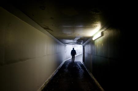 adult rape: Silhouette of a man walking in a tunnel.