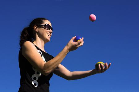 juggling: Young woman juggler is juggling balls. Stock Photo