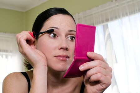 fair complexion: A young caucasian woman looks in mirror and applies mascara makeup. Stock Photo