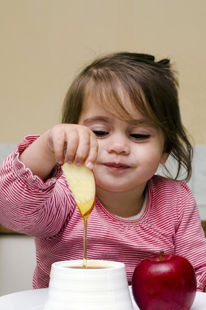 Jewish girl dipping apple slices into honey on Rosh HaShanah the Jewish New Year.