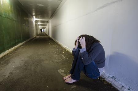 abuso sexual: Escena del crimen Foto del concepto de víctima de violación. Una mujer triste se sienta en el suelo de un túnel oscuro.