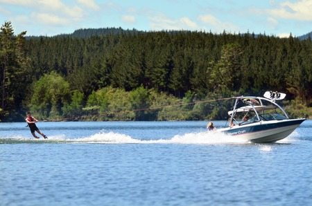 water  skier: A water skier preforming water skiing sport on a lake.