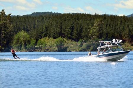 water skier: A water skier preforming water skiing sport on a lake.