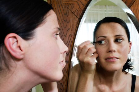 fair complexion: A young caucasian woman looks in the mirror and applies eyeliner makeup. .