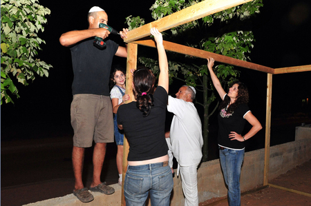 succos: An Israeli family are building a sukka a moments after Yum Kippur was finished. Stock Photo