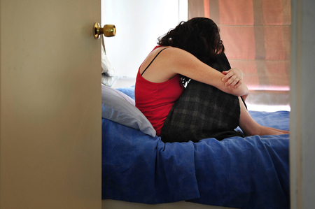 love sad: Depressed young woman sitting on the bed at home suffering from a severe depression