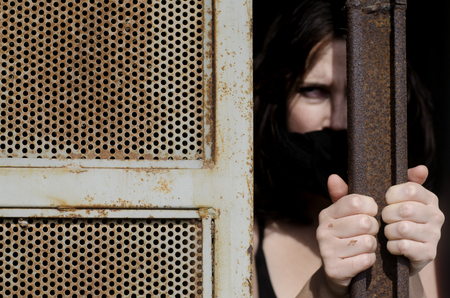 jail cell: A woman trapped in a prison jail cell with a mouth cover Stock Photo