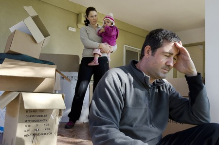 relocating: Young parents and their daughter stand beside cardboard boxes outside their home. Concept photo illustrating divorce, homelessness, eviction, unemployment, financial, marriage or family issues.