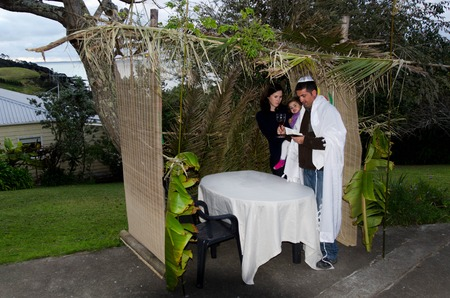tabernacles: Young Jewish family prays at the Sukkah for the Jewish festival of Sukkot. A Sukkah is a temporary structure where meals are taken for the week.