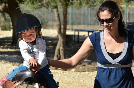 mum and daughter: A baby girl rides pony horse.
