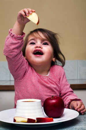 Little Jewish girl dipping apple slices into honey. Its the most popular and well-known Jewish food customs on Rosh HaShanah to express the hope for a sweet new year.