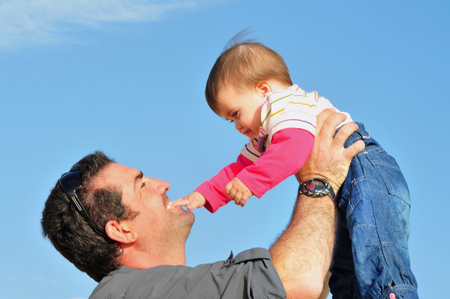 six month old: Father lifts up his baby six month old child in the air and smiles Stock Photo