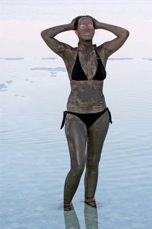 holyland: A young woman in a bathing suit is enjoying the natural mineral mud sourced from the Dead Sea,  Israel.
