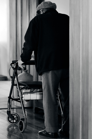 stride: An old disabled elderly man who need additional support to maintain balance or stability while walking use a walker (walking frame) . BW Stock Photo