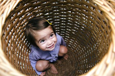 peekaboo: Happy little girl playing peekaboo and hides inside a basket.