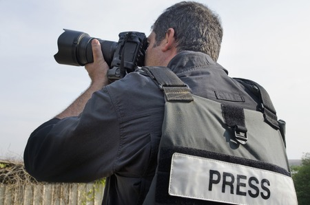 A press photographer takes photos with a professional camera