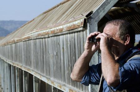 bird watcher: A senior hiker and bird watcher is searching for birds with binoculars.