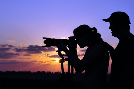 location shot: A photographer is teaching a student wildlife or landscape photography outdoors.