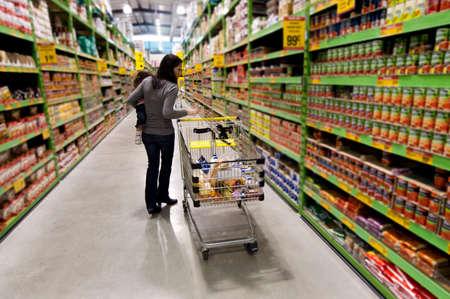 family mart: Cliente femminile tiene il suo bambino mentre lo shopping in un supermercato con carrello. Archivio Fotografico