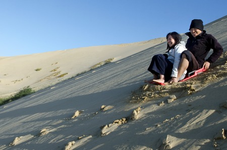 quicksand: Man and woman rolled down the slope of snow-white  Te Paki sand dunes in Northland New Zealand.
