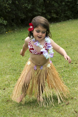 hula girl: Little girl with Hawaiian Costume  of hula dancer, Hula girl dancing outdoor in the garden over green grass barefoot.