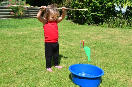 home garden: Adorable little girl is playing fishing game in the home garden.