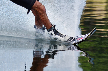 water skiers: A close up of a slalom water skiers legs and skis with water splash.