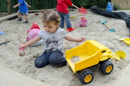 sandpit: Adorable little girl plays with toy on the sandpit in the kindergarten.