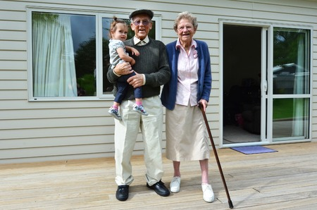 Smiling grandparents holding their grandchild outside their home.