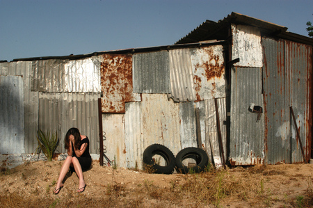 adult rape: A woman who is a victim of abuse is sitting on outside an old shed sad and depressed