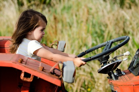 Little girl drive an old tractor.